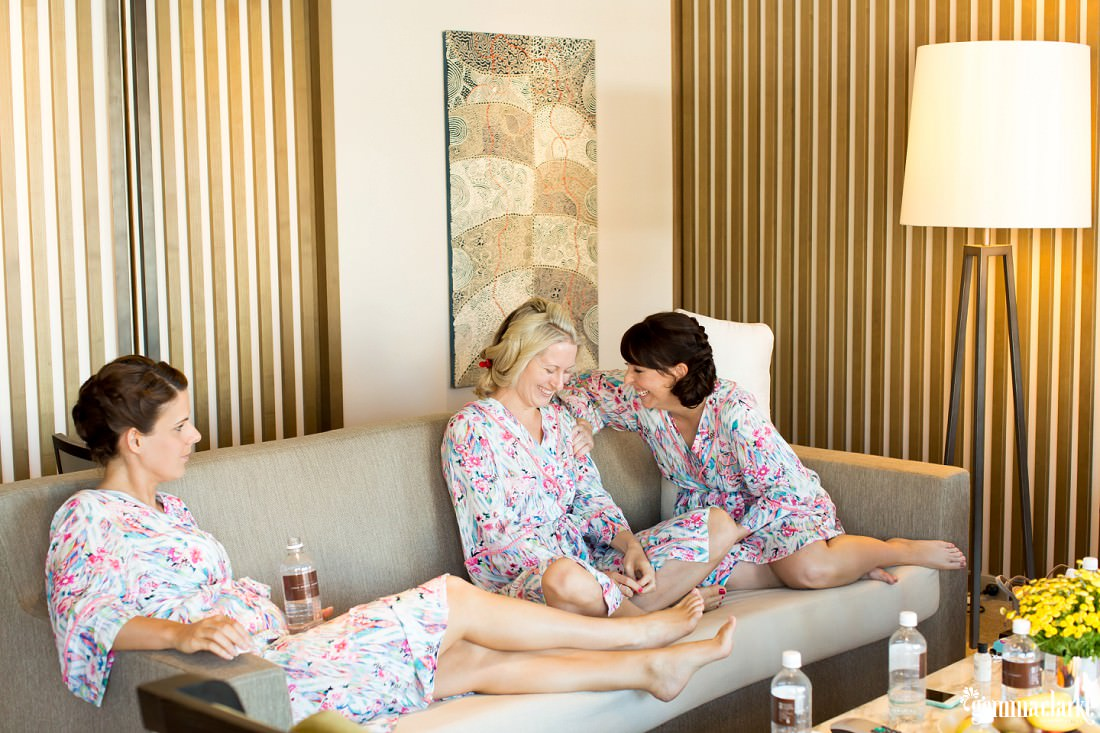 Three women in robes sitting and laughing together on a couch
