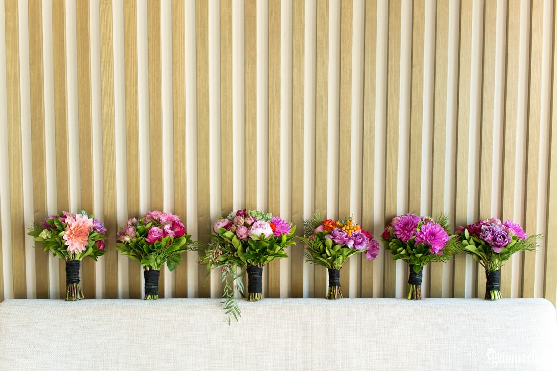 Six bouquets of purple and pink flowers standing against a wall