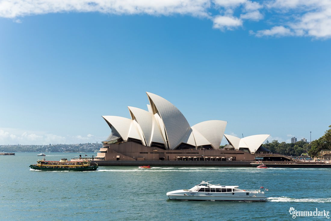 A side profile of the Sydney Opera House on a bright sunny day with some ferries and boats passing in the foreground and background