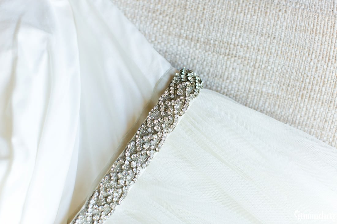 A closeup of a bridal gown showing the detail of the belt