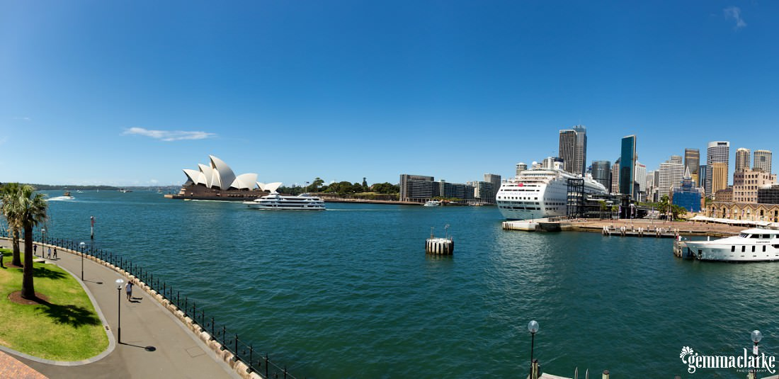 A view of Circular Quay with the Sydney Opera House on the left and a large cruise-liner docked on the right