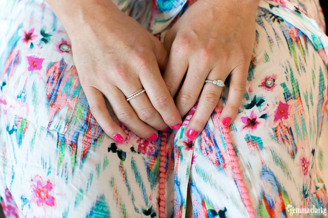 A close up of a woman's hands showing her bright pink nail polish