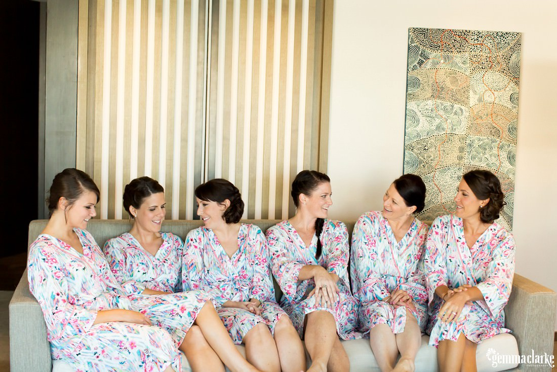 Six women in robes sitting on a couch and smiling at each other
