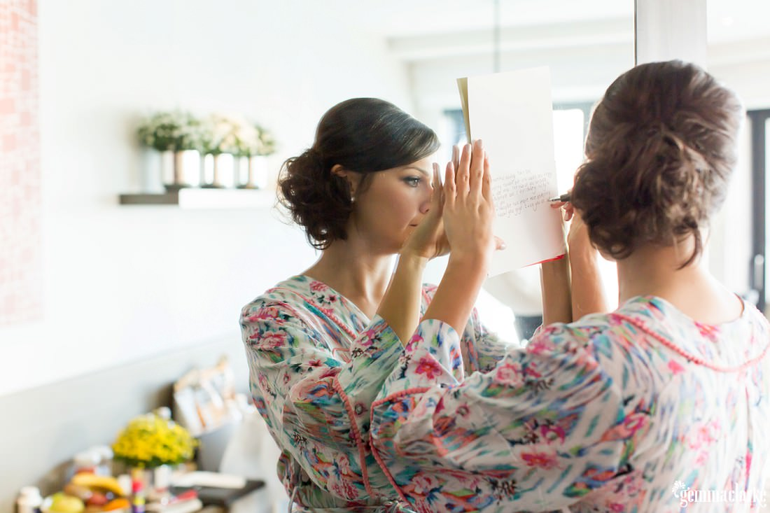 A woman in a robe holding a card against a mirror as she writes in the card