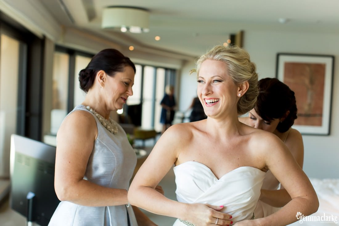 A bride smiling as her mother and a bridesmaid help her fasten the back of her wedding gown