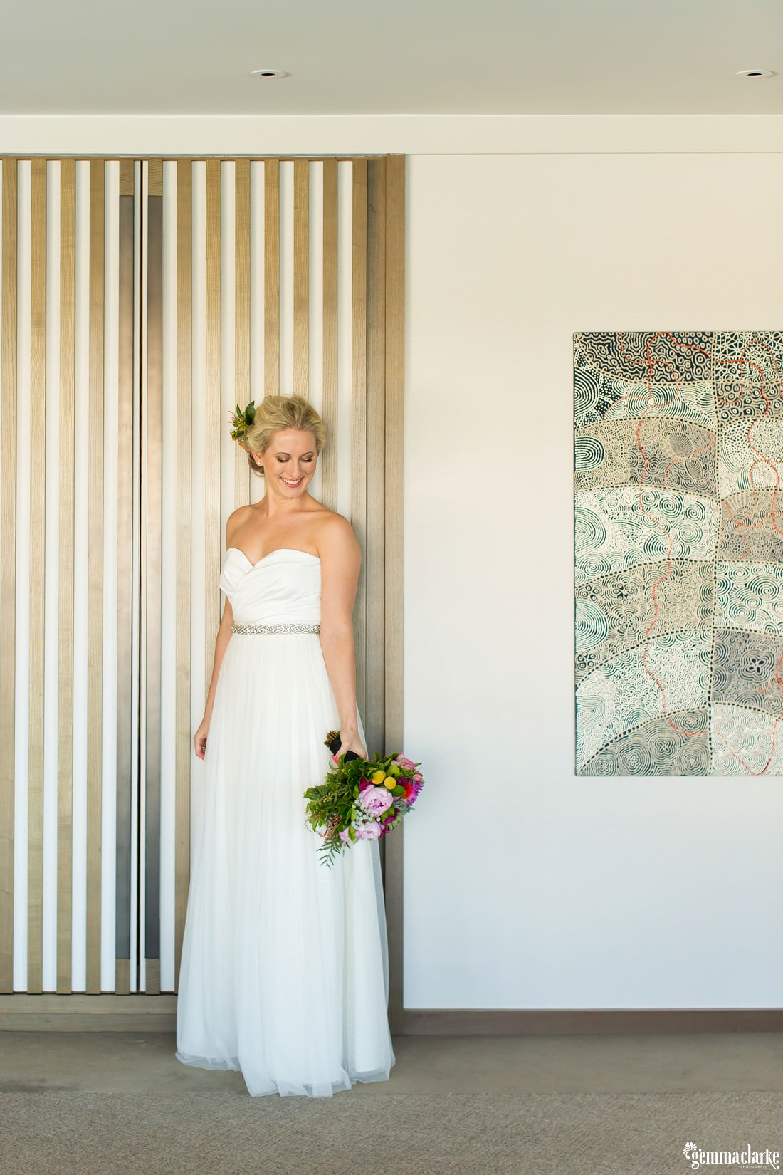 A bride in her wedding gown standing and smiling as she looks down at her bouquet