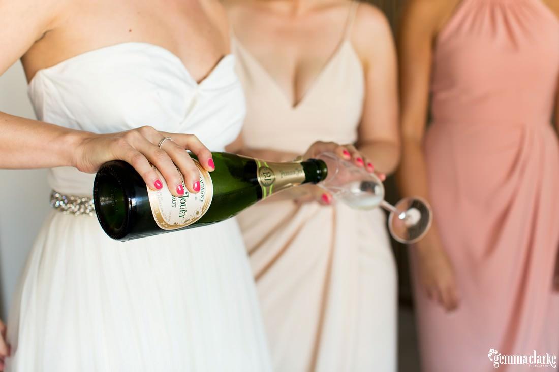 A bride pouring champagne into a flute