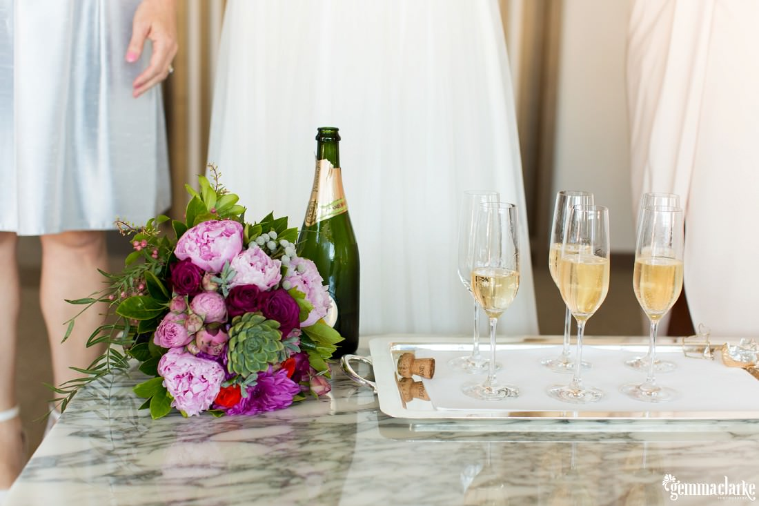 A tray of champagne flutes on a table next to a champagne bottle and a bouquet of flowers