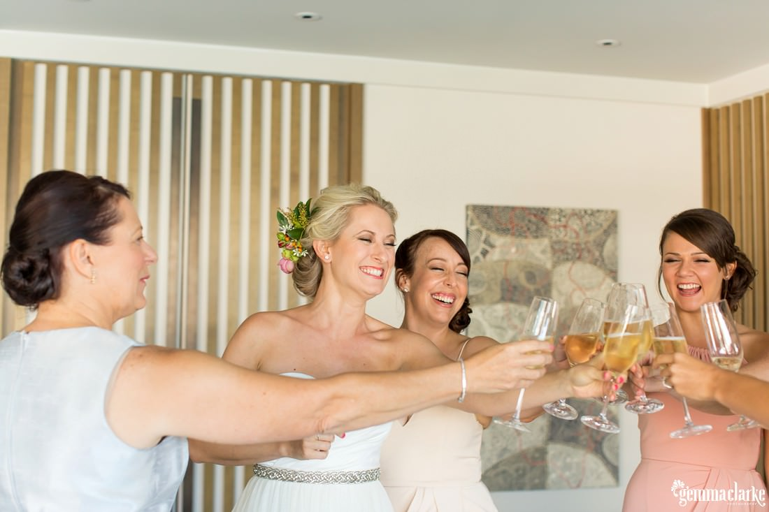 A bride and her bridesmaids smiling as they clink their champagne flutes together