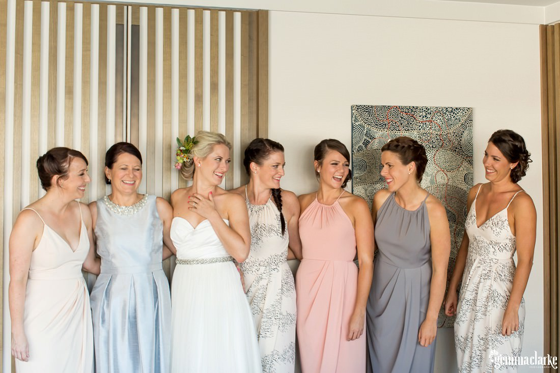 A bride, her mother and her bridesmaids looking at each other and smiling