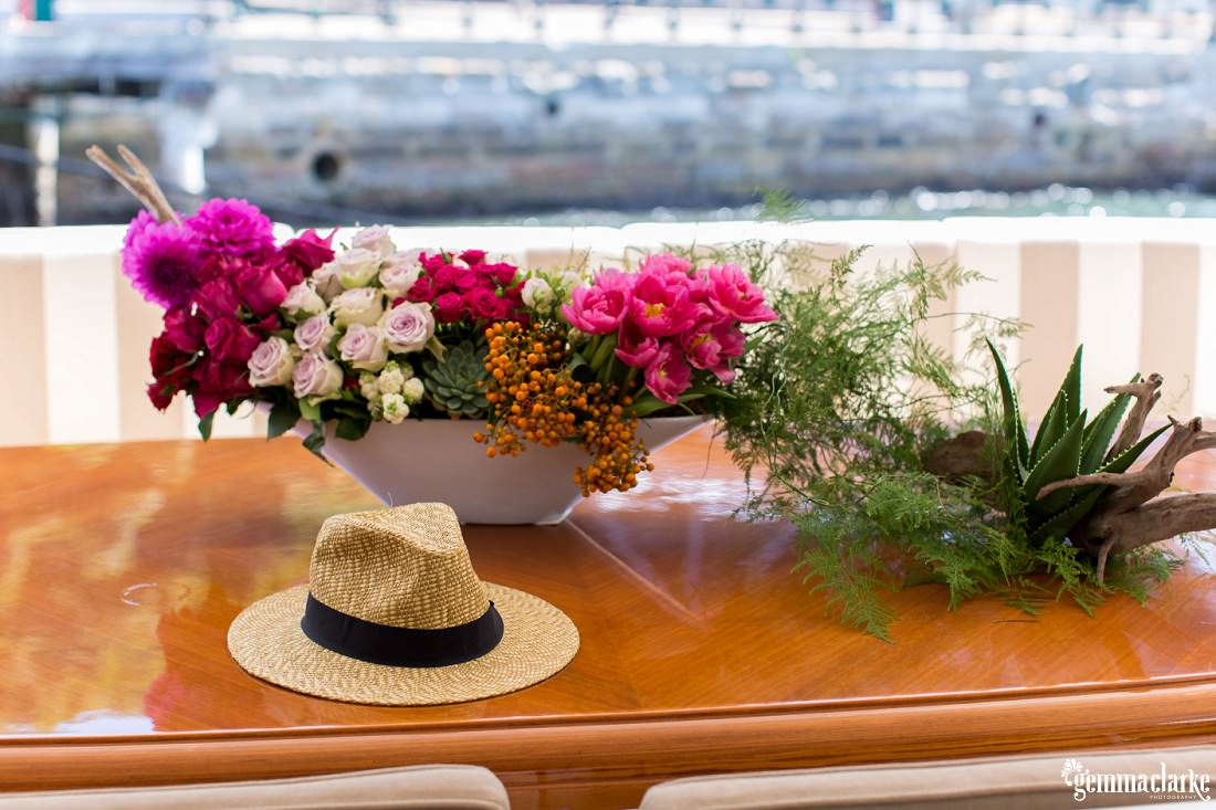 A bowl of flowers and a straw hat on a table