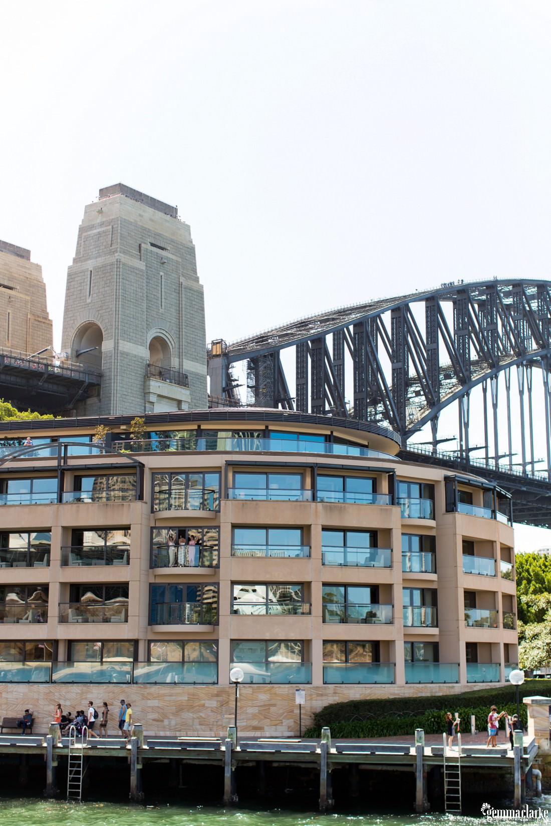 A distant shot of bridesmaids waving from the balcony of a hotel with the Sydney Harbour Bridge in the background