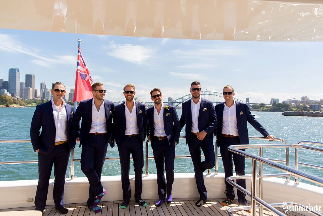 A groom and his groomsmen stand smiling at the rear of a boat with the Sydney Harbour Bridge in the background