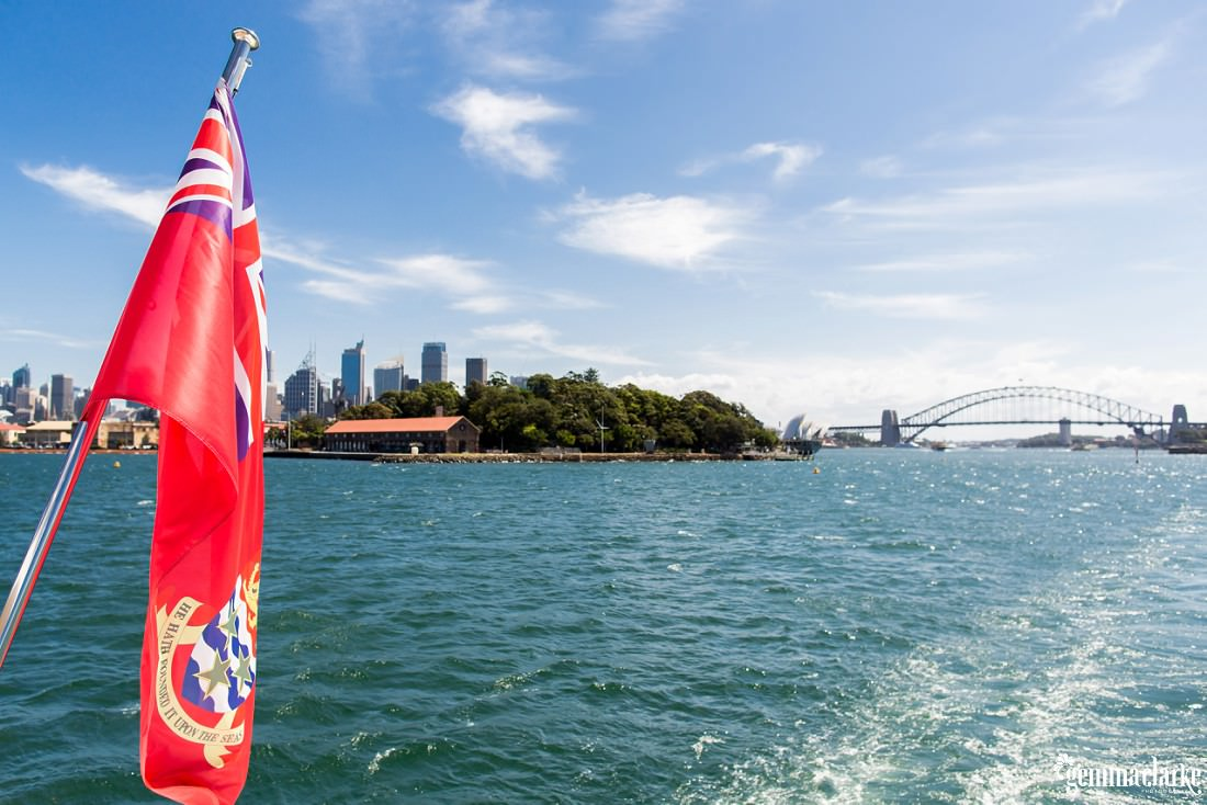 An image of Sydney taken from the back of a boat on Sydney Harbour, with the city on the left and Sydney Harbour Bridge on the right