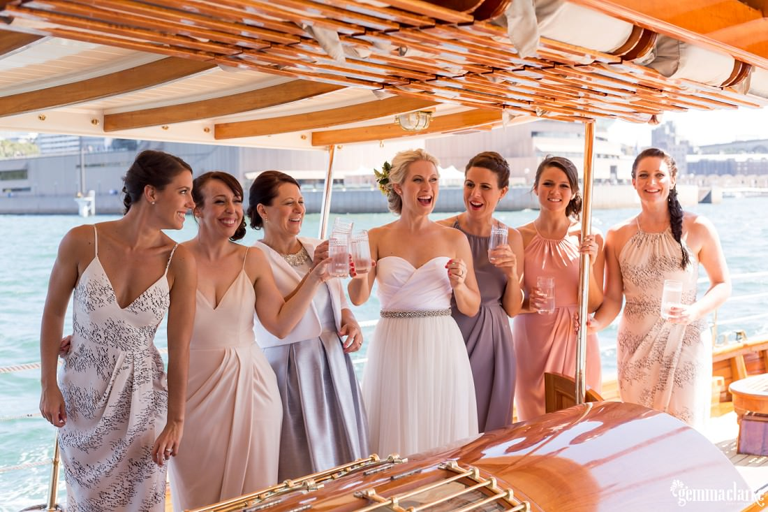 A bride, her mother, and her bridesmaids smiling as they stand on a boat