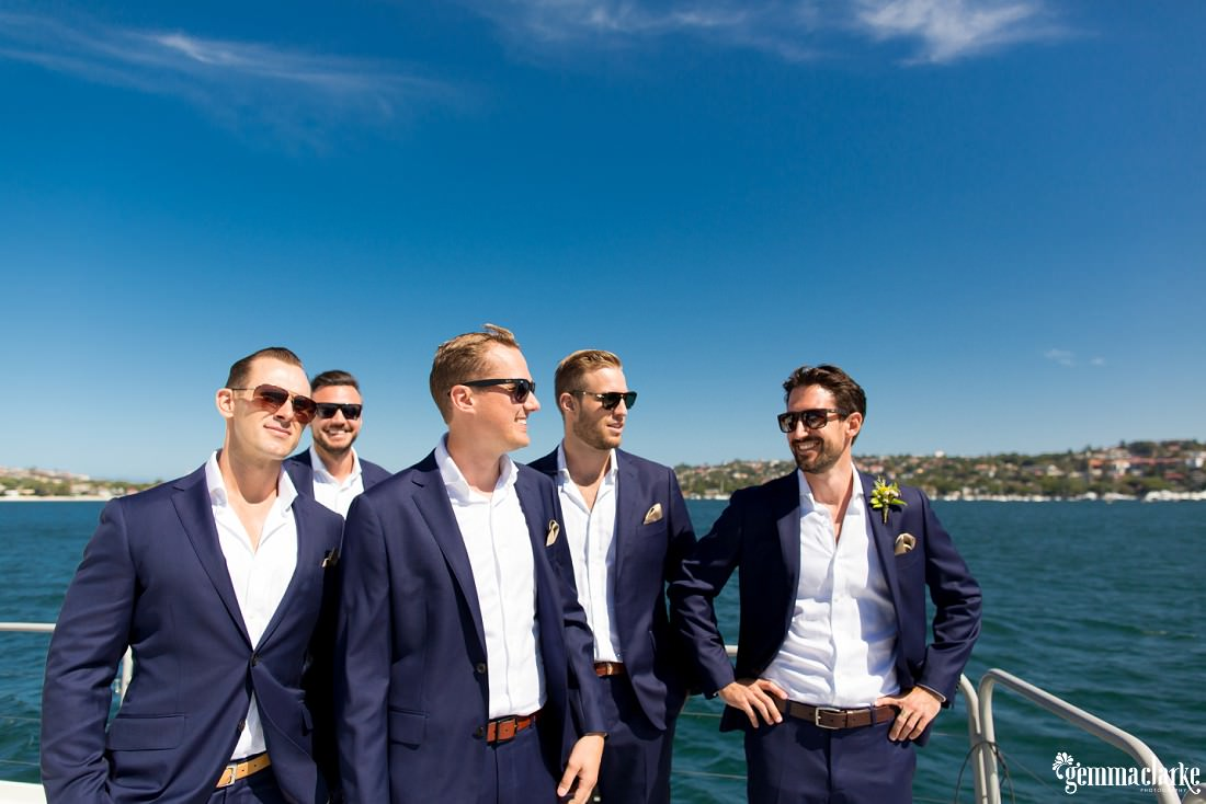 A groom and his groomsmen smiling as they stand on a boat