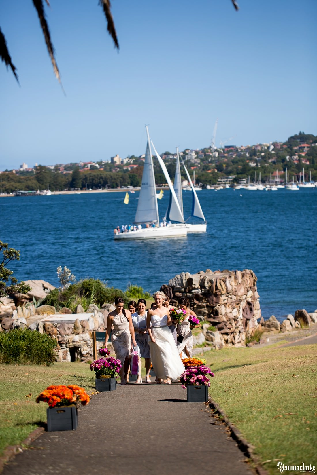 A bride and her bridesmaids walking up a path with two yachts sailing past in the background, Shark Island Wedding