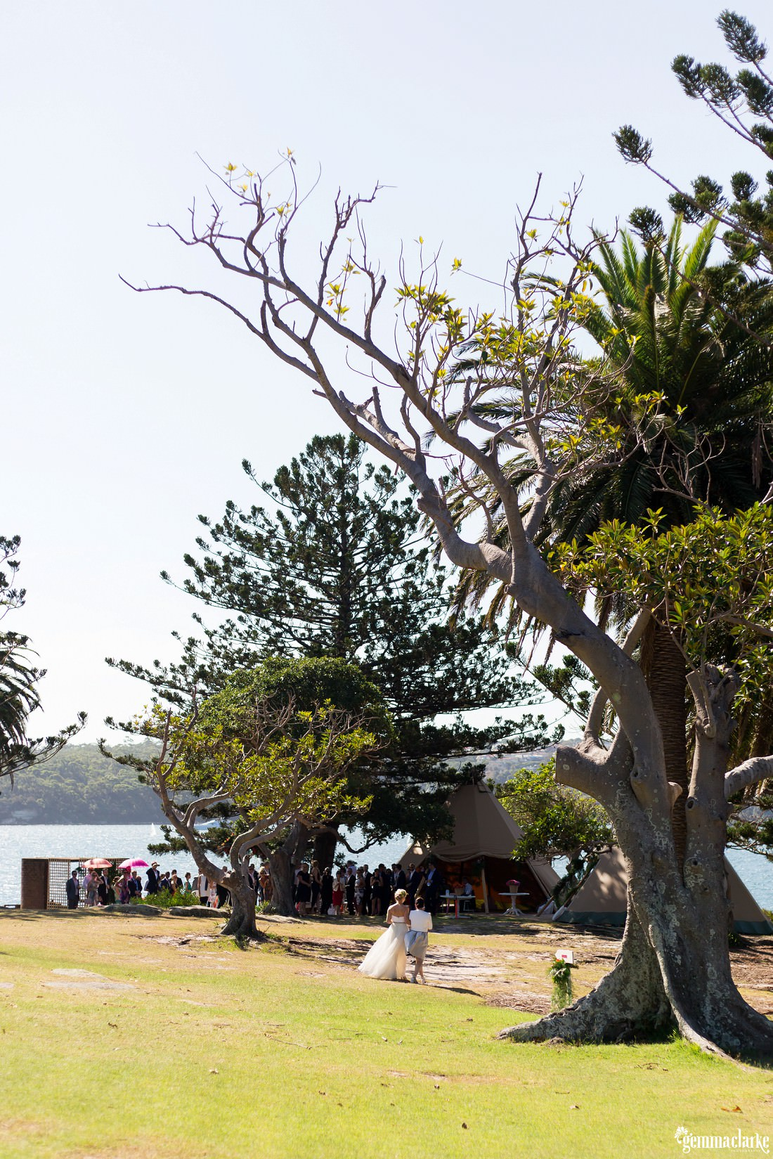 A bride is walked towards her wedding ceremony with all the guests looking on, Shark Island Wedding