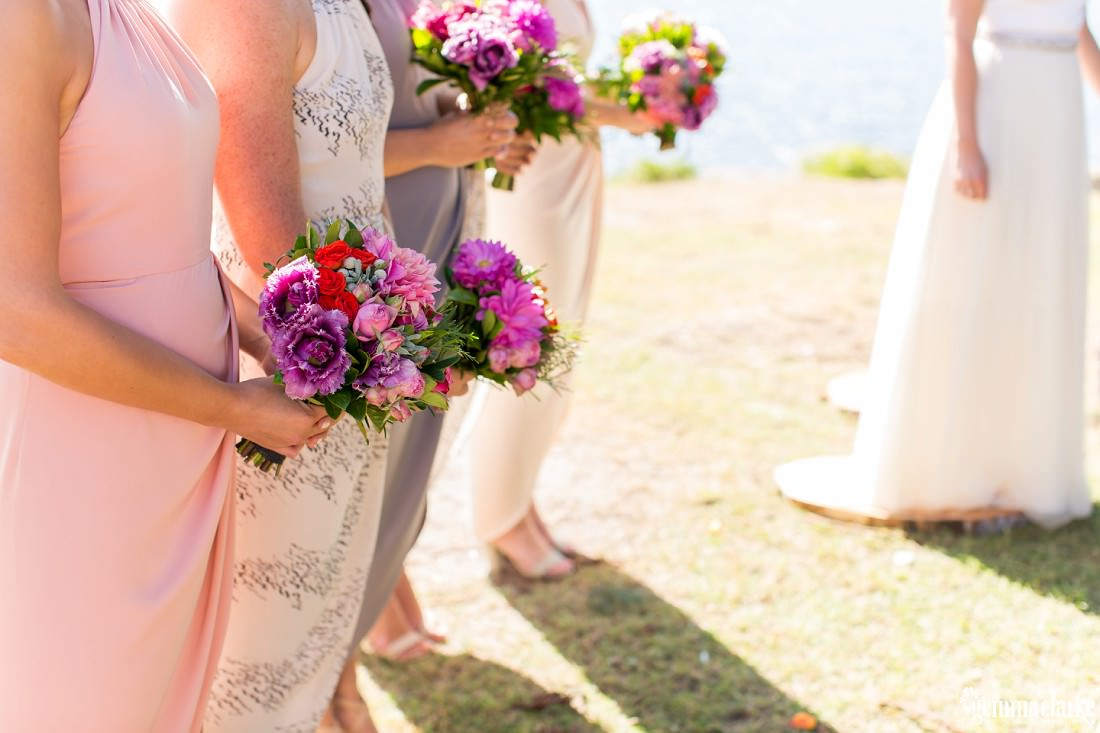 Closeup of bridesmaids holding their bouquets in front of them during a wedding ceremony