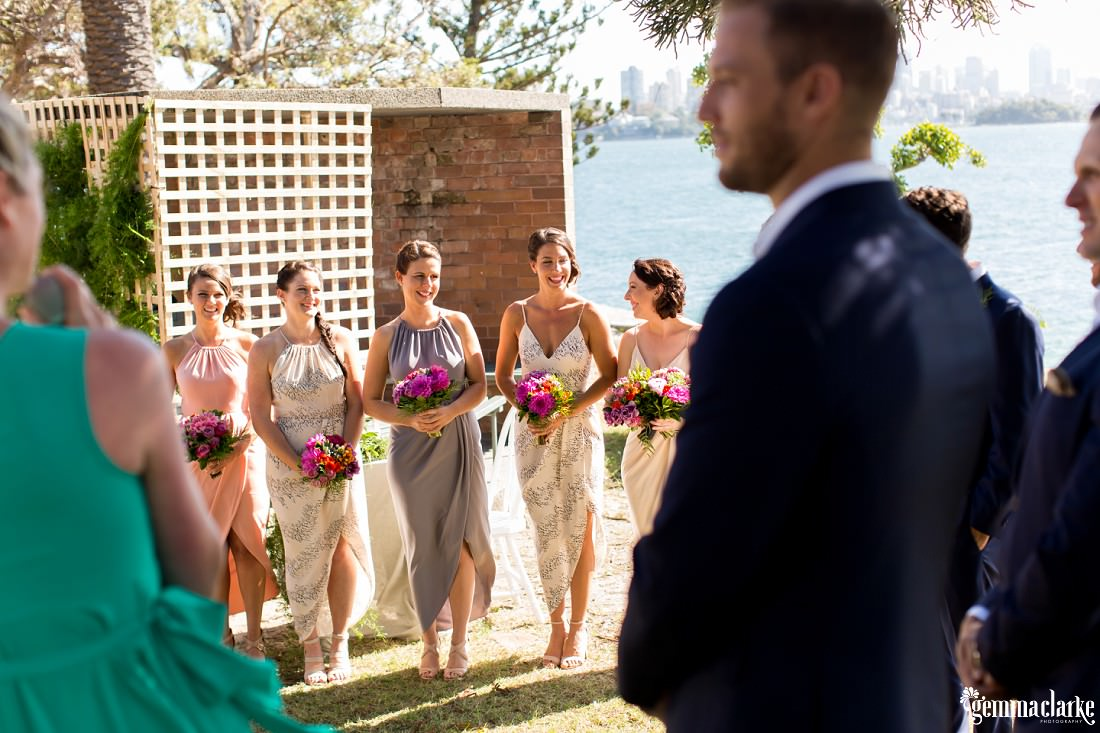 Bridesmaids smiling to each other during the ceremony at a Shark Island Wedding