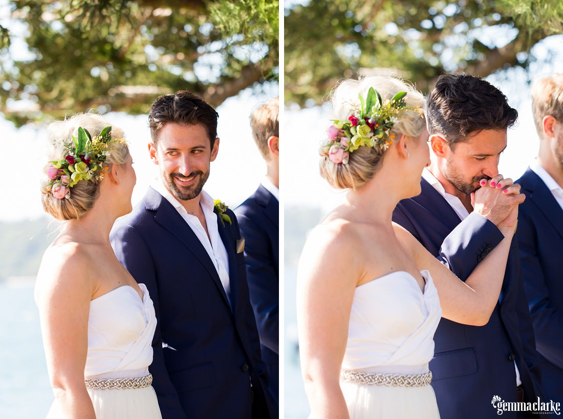 A groom smiles at his bride during their wedding ceremony and then kisses her on the hand