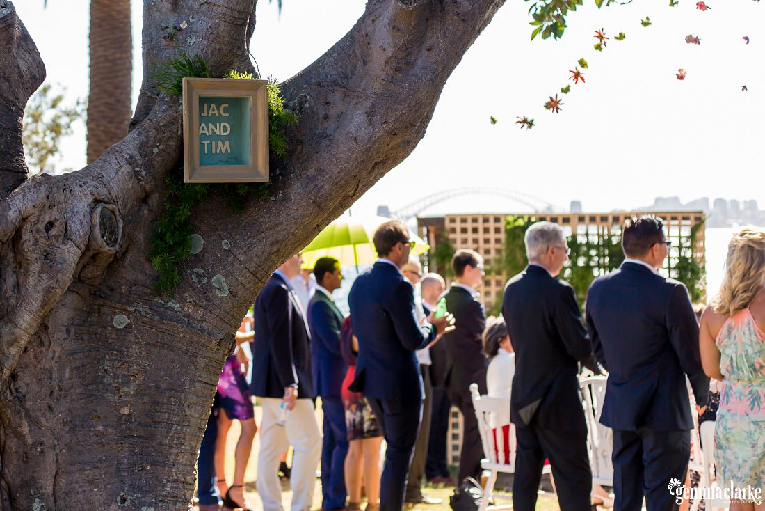 A wedding sign hangs from a tree as wedding guests watch the ceremony in the background