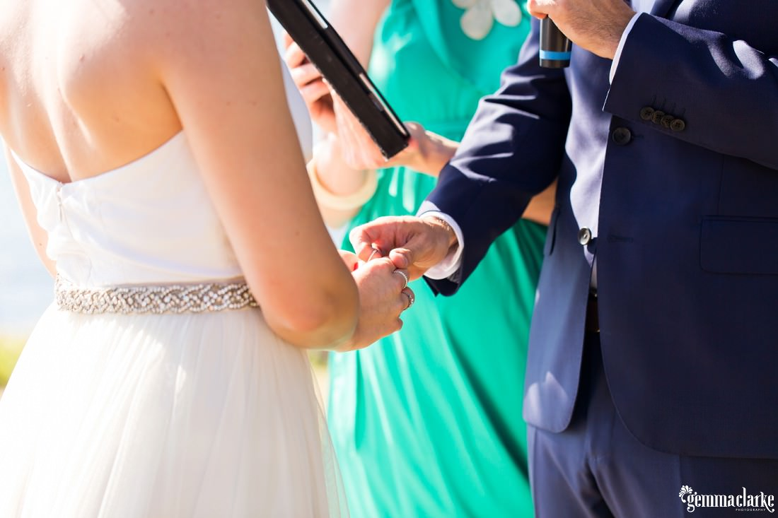 A groom putting a ring on his bride's finger