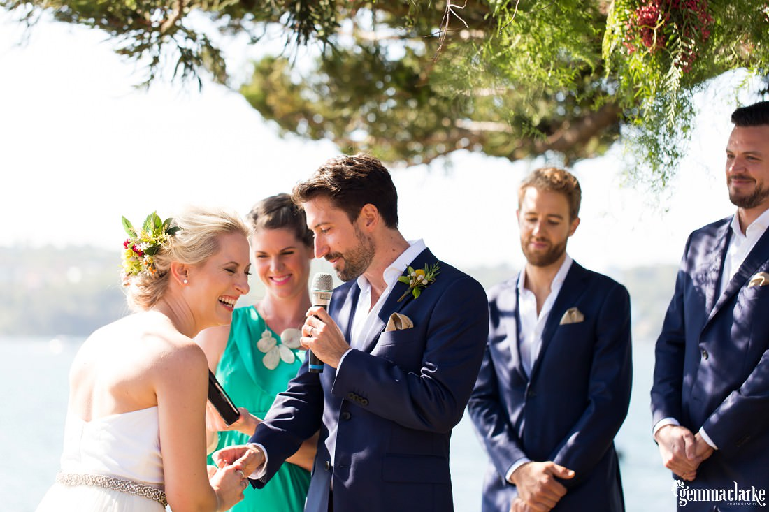 A groom putting a ring on his bride's finger as she laughs