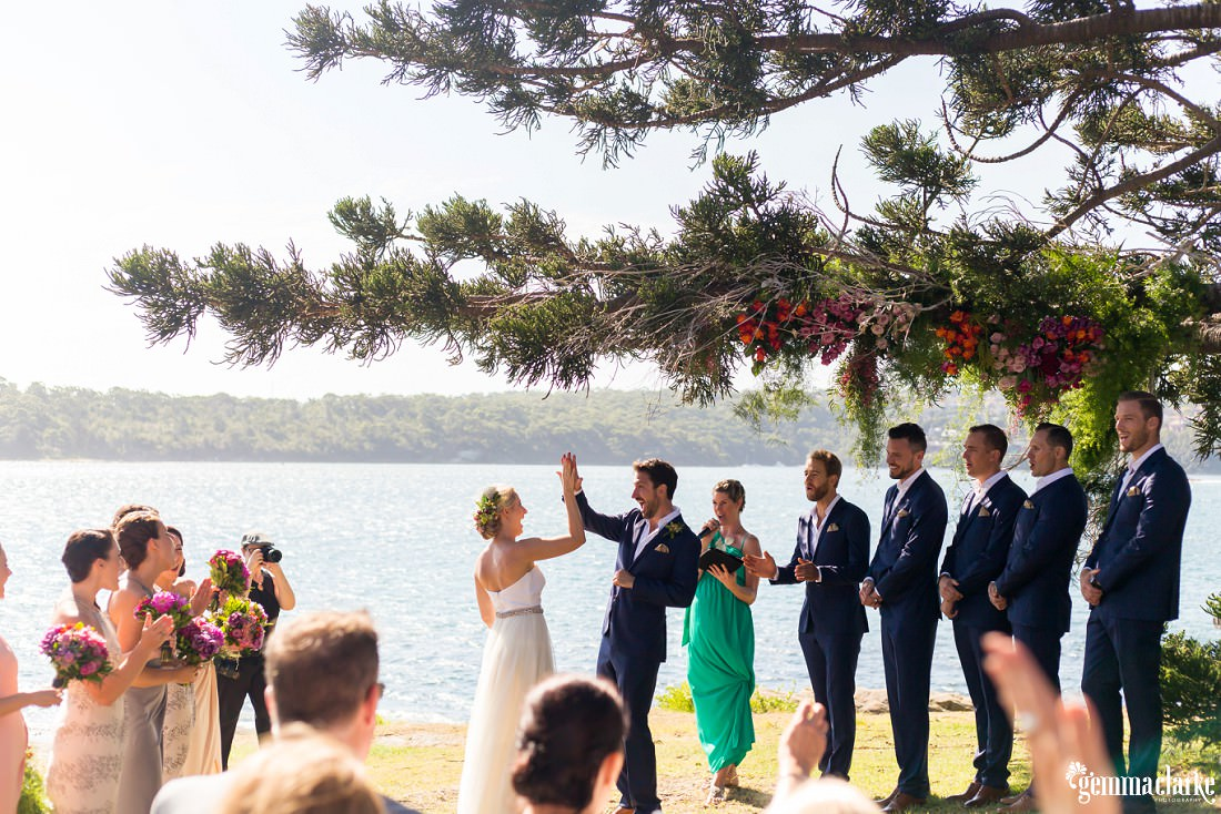 A bride and groom share a high five during their ceremony as their bridal party looks on