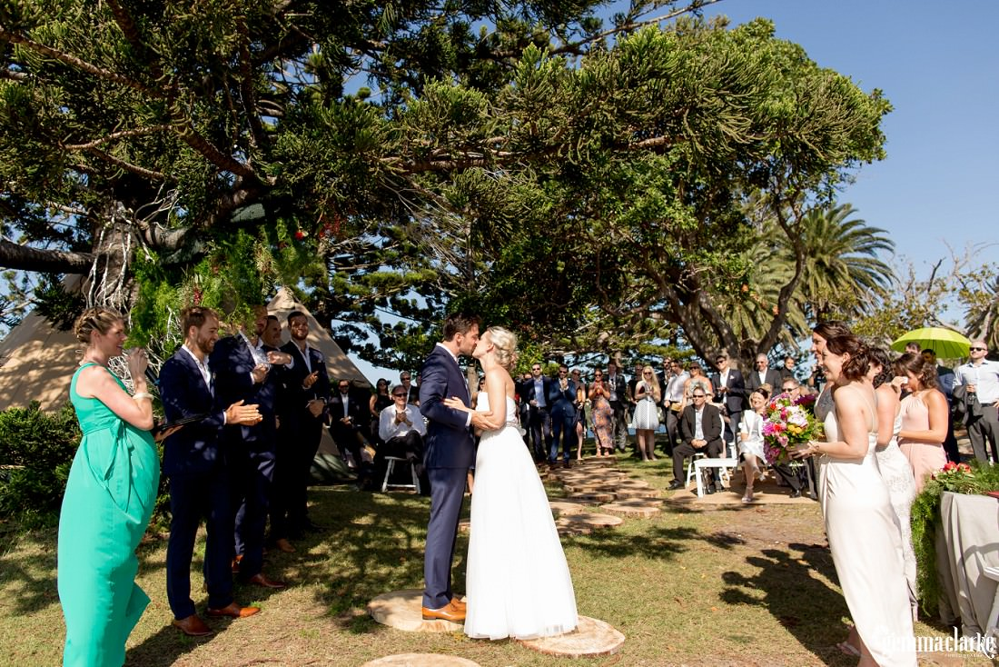 A groom kisses his bride during their Shark Island Wedding ceremony