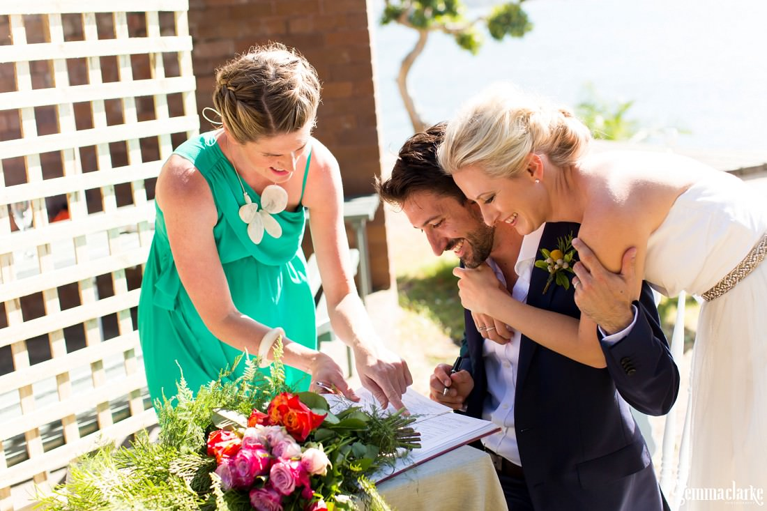 A smiling groom is shown by the celebrant where to sign his wedding papers as his bride leans over his shoulder