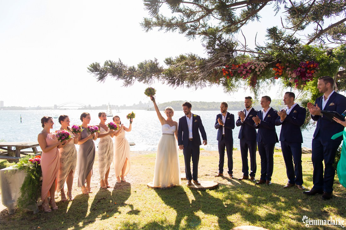 A bride holds her bouquet in the air in celebration as the bridal party cheers, Shark Island Wedding