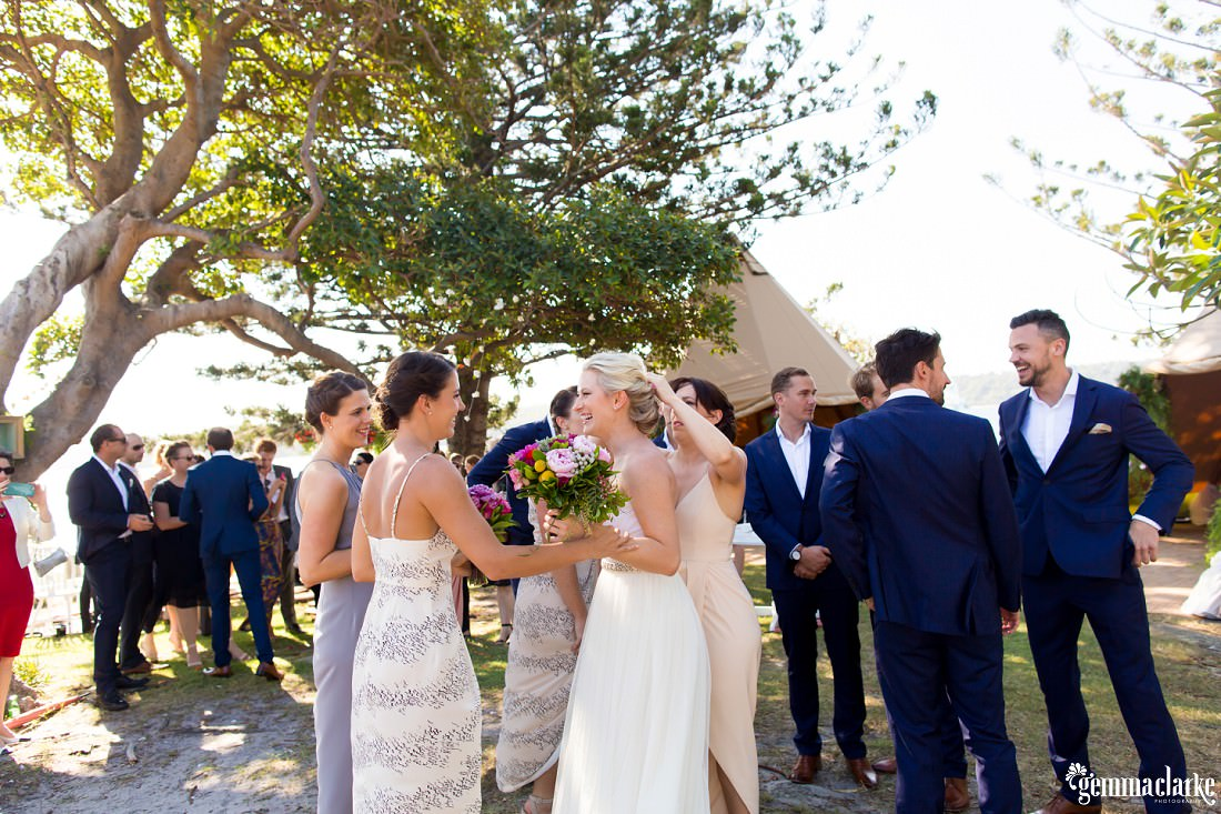 Wedding guests mingle under a tree