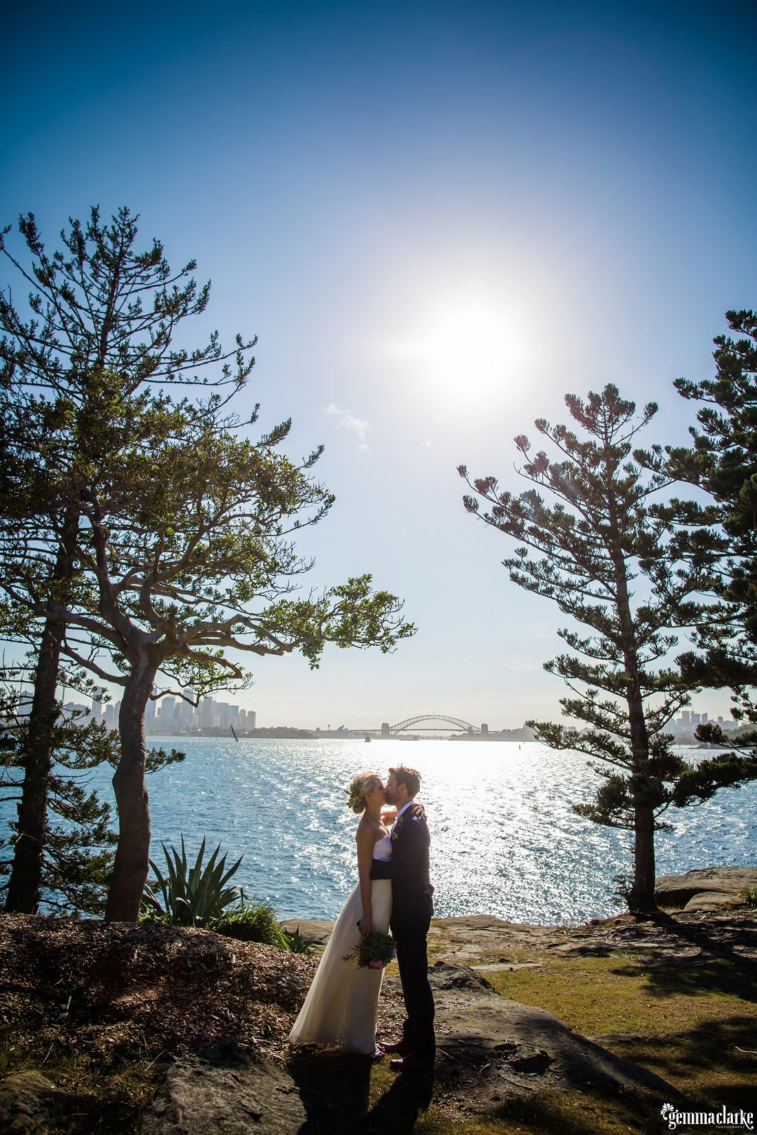 A bride and groom kissing with Sydney Harbour and the bridge in the background, Shark Island Wedding