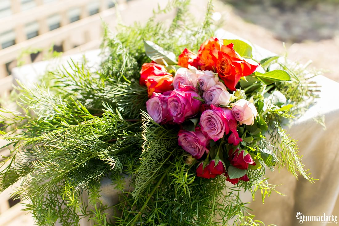 A bunch of pink, red and orange flowers on a table