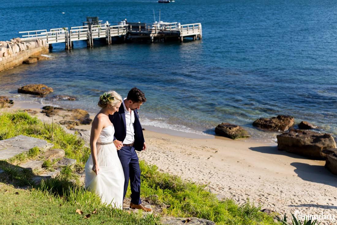 A bride and groom descending cement stairs to a small beach on Shark Island