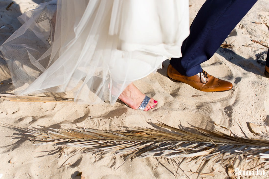 A closeup of a bride and groom's shoes as they walk along a sandy beach