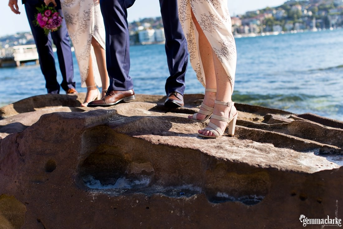 A closeup of bridesmaids' and groomsmens' shoes as they stand on large rocks on a beach