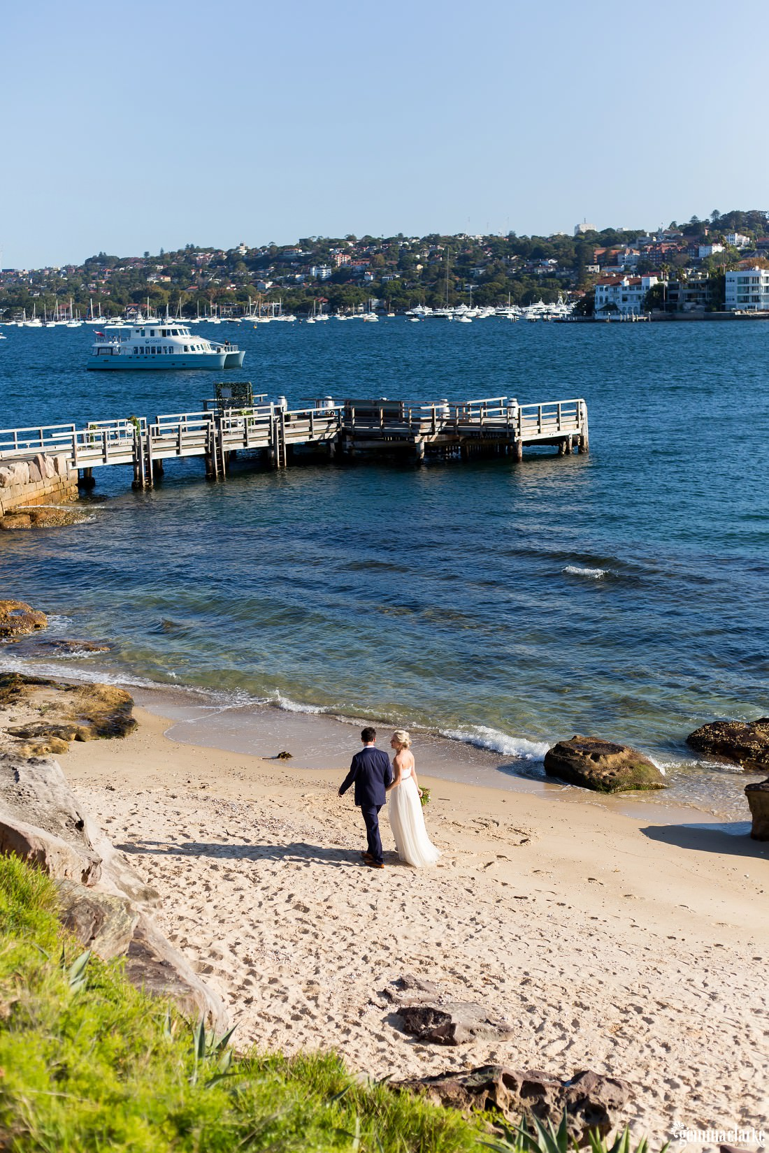 A bride and groom walking along a beach with the water and jetty in the background, Shark Island Wedding