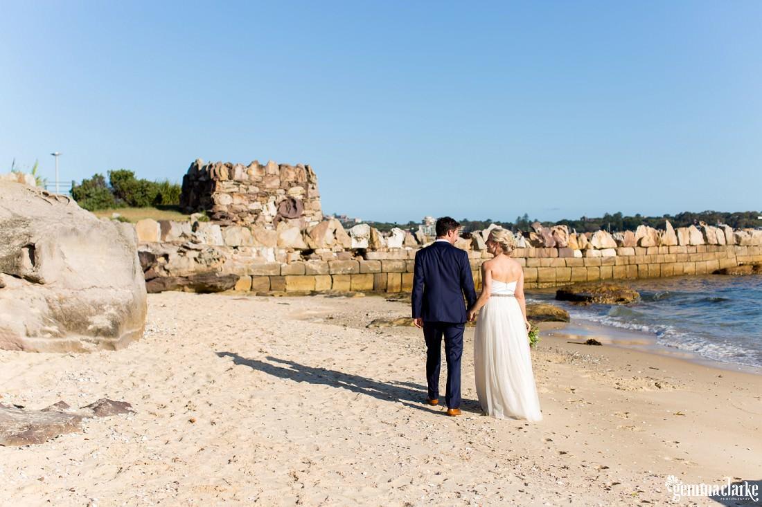A bride and groom walking along a beach on Shark Island