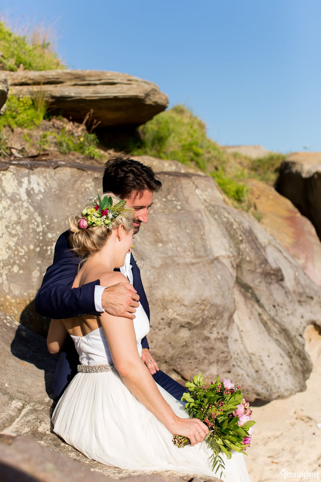 A groom with his arm around his bride's shoulders as they sit on a large rock on a beach