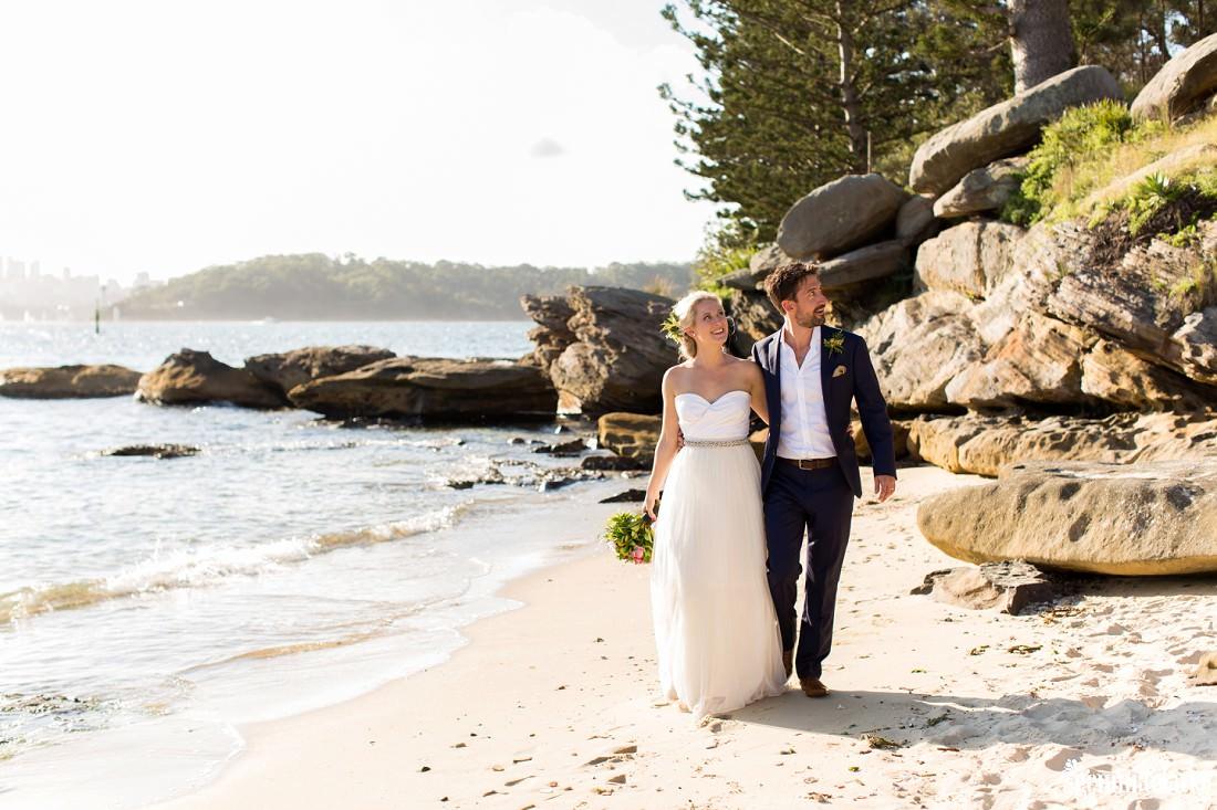 A bride and groom walk along a beach arm in arm, Shark Island Wedding