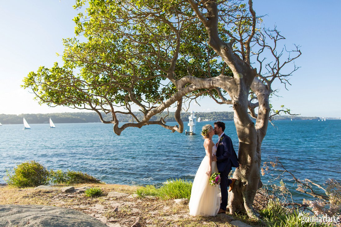 A bride and groom kiss under a tree near the water