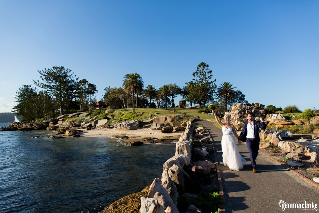 A bride holds her bouquet in the air and the groom pumps his fist in celebration as they walk down a pier, Shark Island Wedding