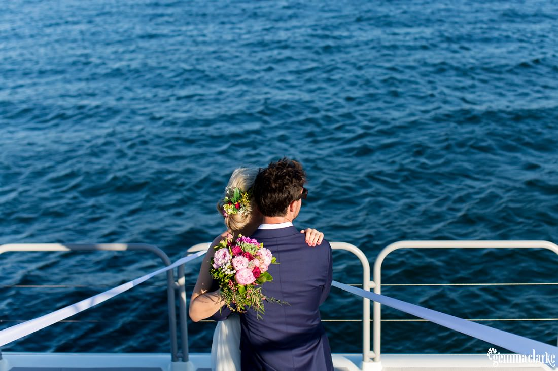 A bride and groom embrace on a boat as they look out to the water, Shark Island Wedding