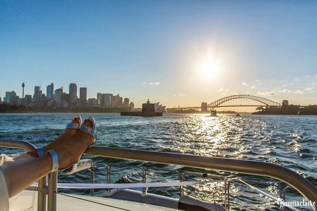 A bride rests her sparkly high heels on the railing of a boat on Sydney harbour with the city and the Sydney Harbour Bridge in the background, Shark Island Wedding