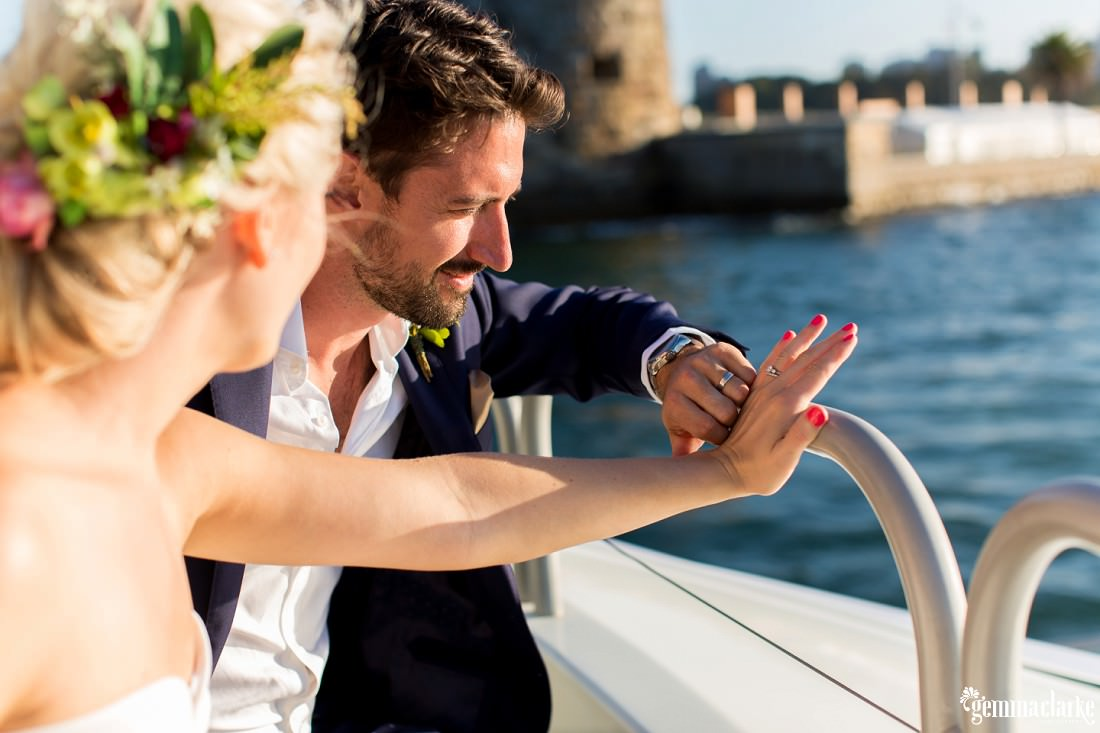 A bride and groom on a boat looking at their wedding rings