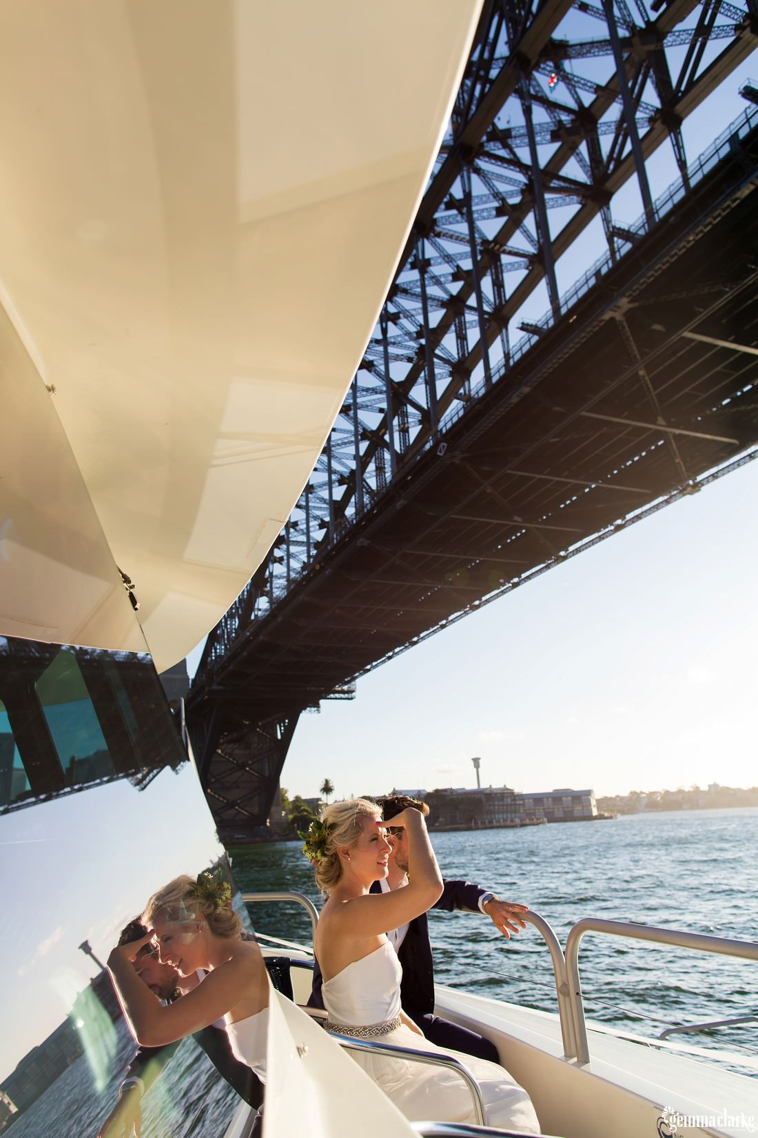 A bride and groom look out from the front of a boat as it passes beneath the Sydney Harbour Bridge