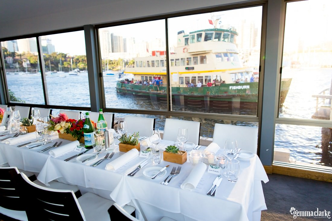 Table settings at a wedding reception as a ferry can be seen arriving through a window in the background