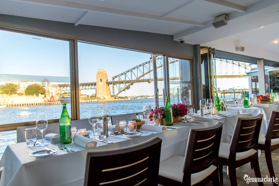 Table settings at a wedding reception. Sydney Harbour Bridge can be seen through a window in the background.
